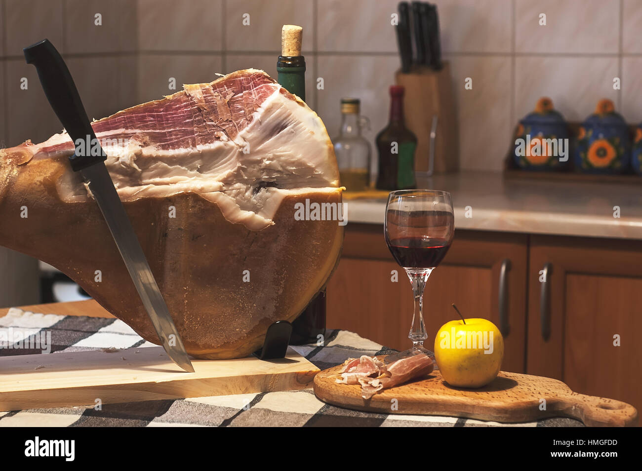 Spanish Jamon Serrano on wooden tabla jamonera with knife, apple, glass and bottle of red wine. Home cooking, food - Stock Image