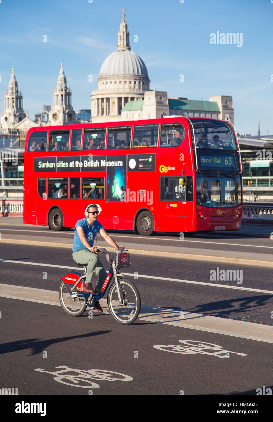 young man riding Santander hire bike on cycle superhighway 6 on Blackfriars bridge, London, with red bus and St Stock Photo