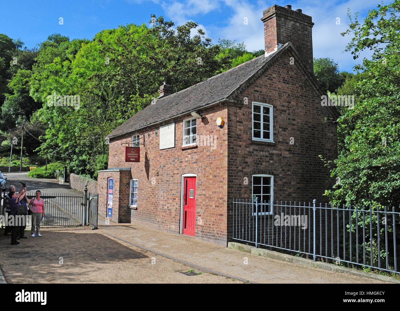 Visitors looking at the Old Toll House at the end of the bridge.  Ironbridge.  Shropshire. - Stock Image