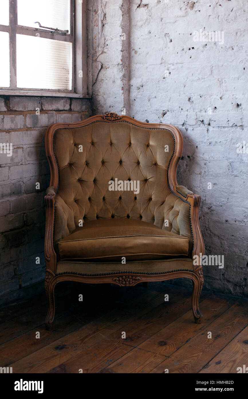 A day-lit Victorian green velvet armchair in a studio space. - Stock Image