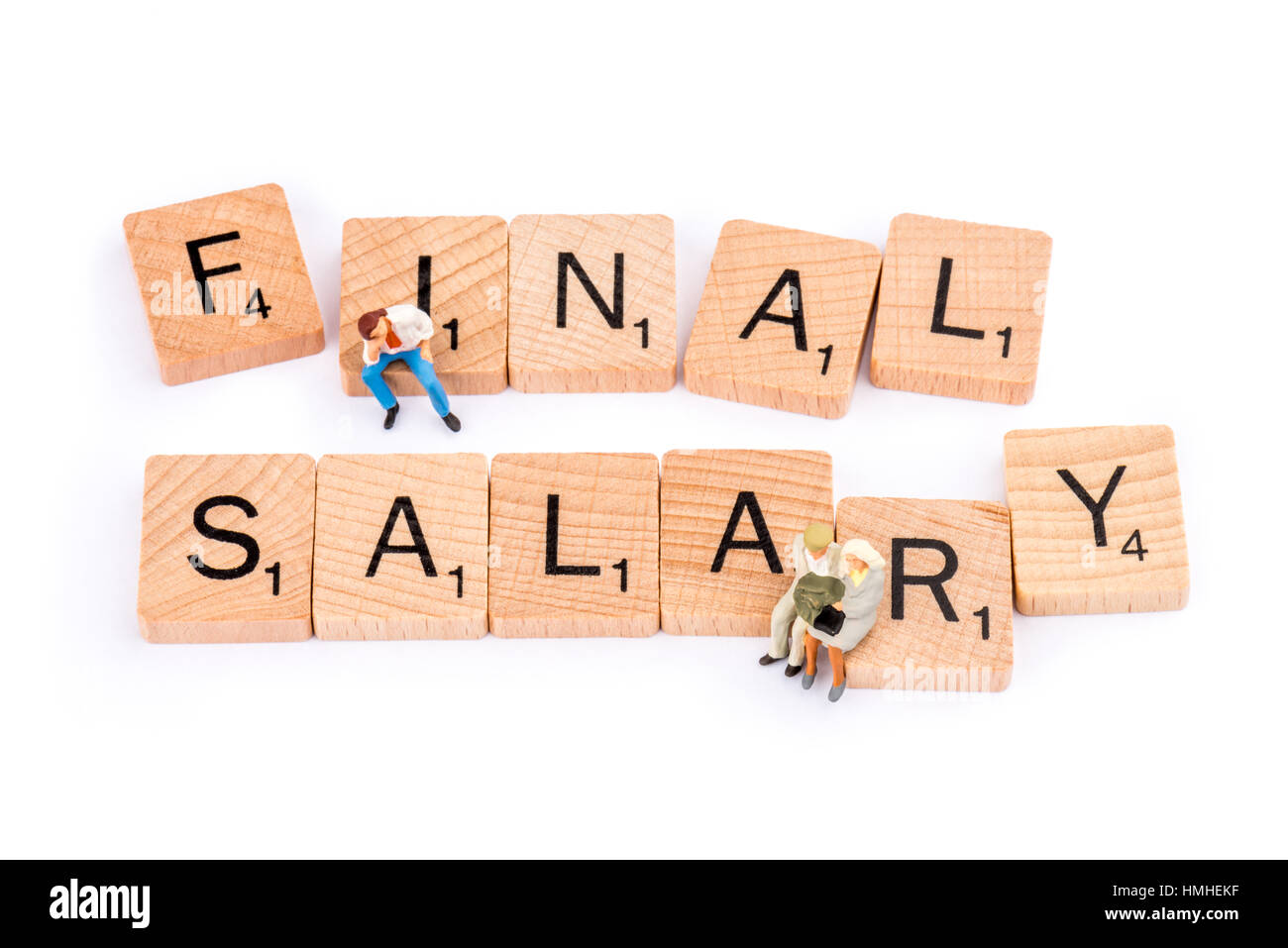 Scrabble letters make up the word FINAL SALARY. A young man sits on  on the letter I whilst an elderly couple sit - Stock Image