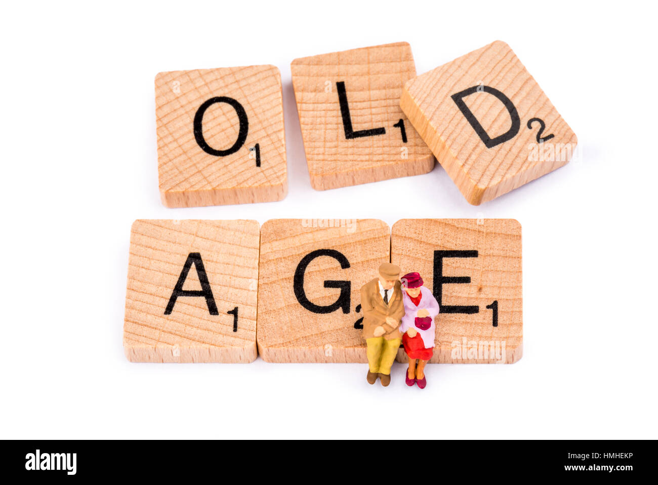 Scrabble letters make up the word OLD AGE. An elderly couple sit on the word AGE. Stock Photo