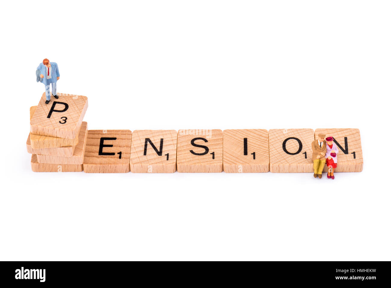 Scrabble letters make up the word PENSION. A man stands on top of the letter P of PENSION, whilst an elderly couple - Stock Image