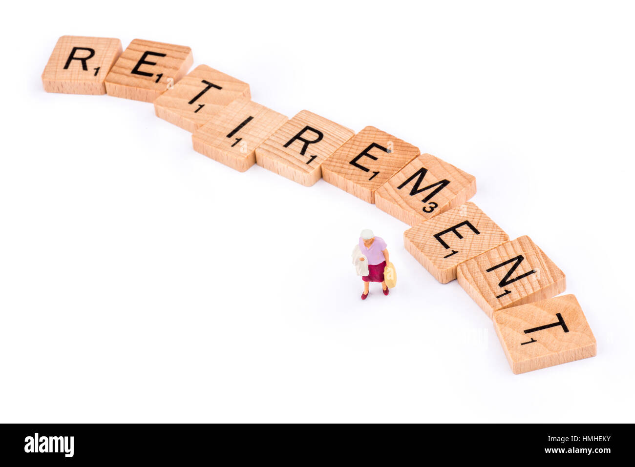 Scrabble letters make up the word RETIREMENT. An elderly lady walks away from the letter E. - Stock Image