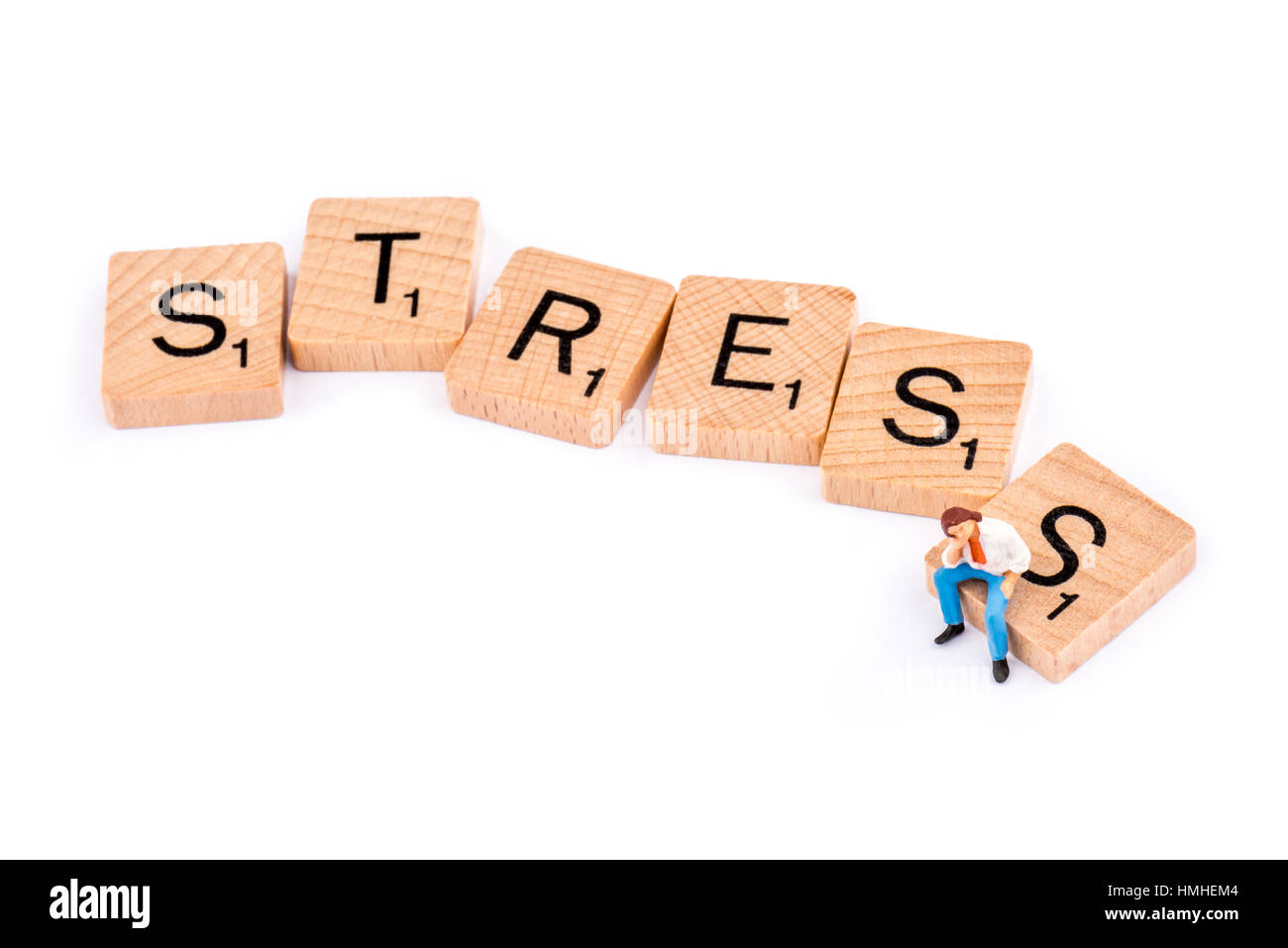 Scrabble letters make up the word STRESS. A young man sits alone on the letter S. - Stock Image