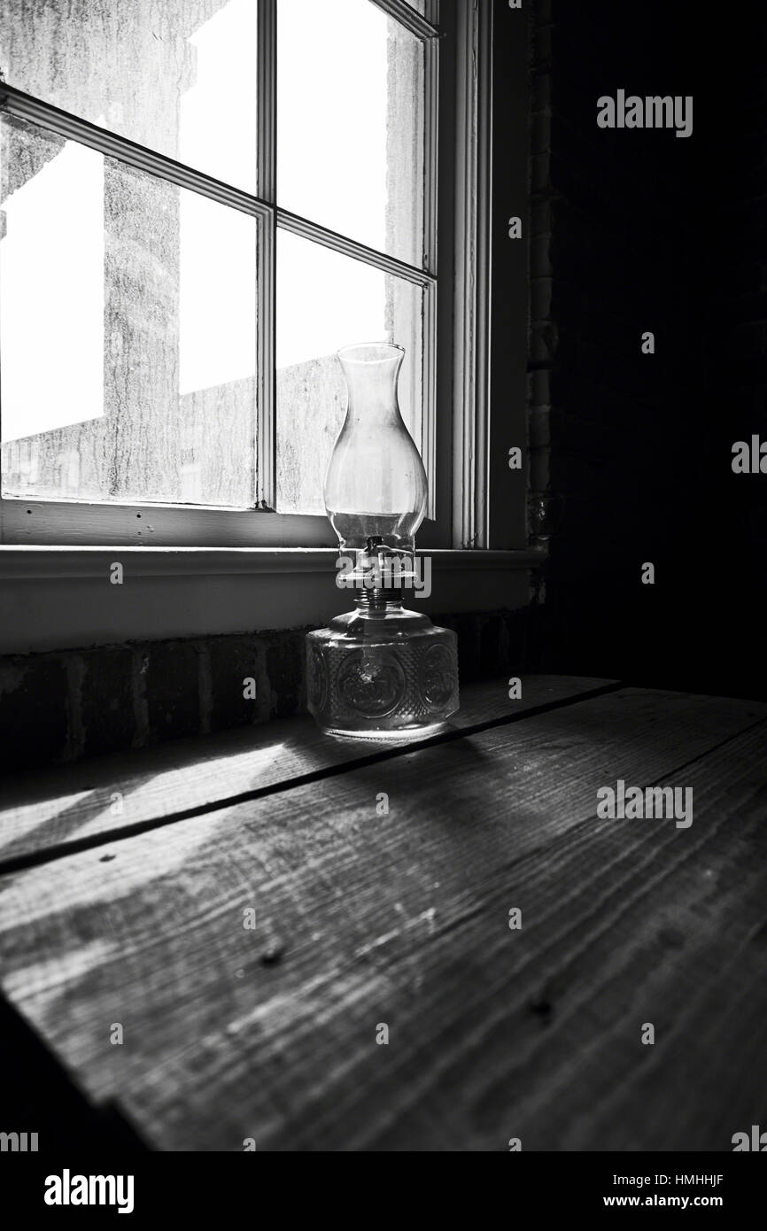 Low Angle View of an Old Glass Oil Lamp on a Wooden Dest at a House Window - Stock Image