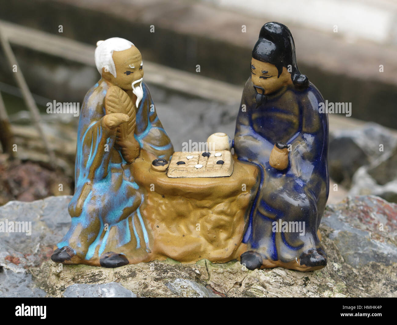 Ceramic ornament of two old Asian men playing chess Stock Photo