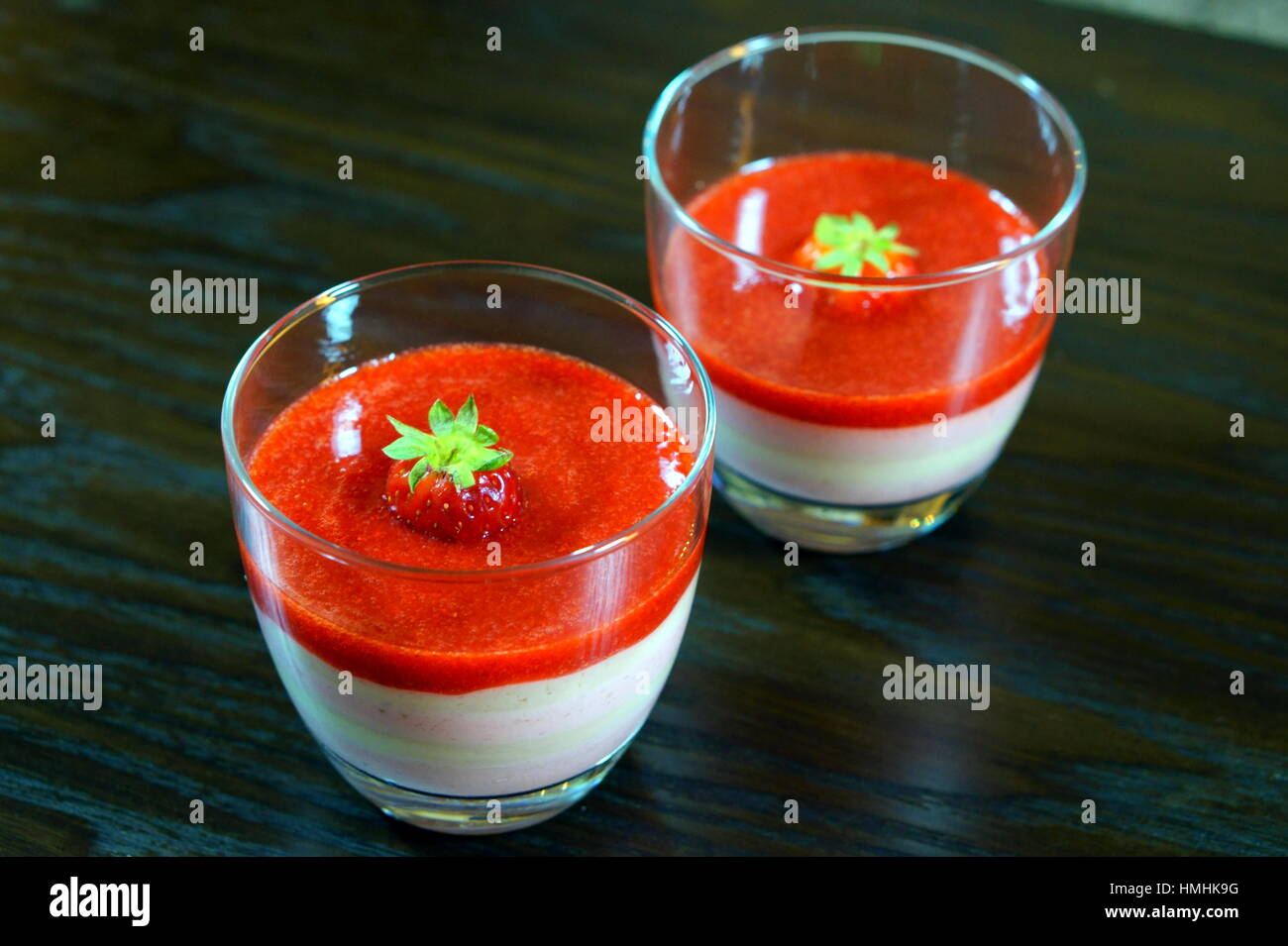 Tricolour strawberry and banana cream milkshake in mixed light lying on a dark wooden table - Stock Image
