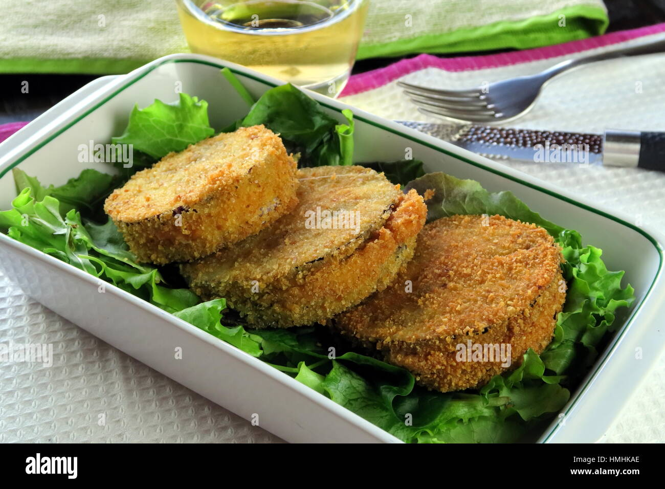 Aubergine and melted cheese vegetarian deep fried Cordon Bleu served in a white baking dish - French / Italian recipe - Stock Image