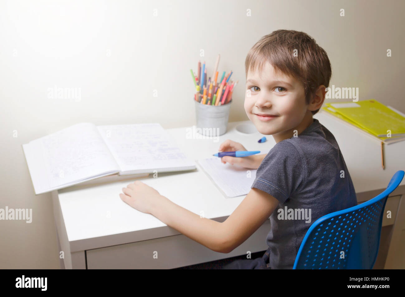 Happy little boy writting. Child sitting at the desk home and doing his homework. School, children, education concept - Stock Image