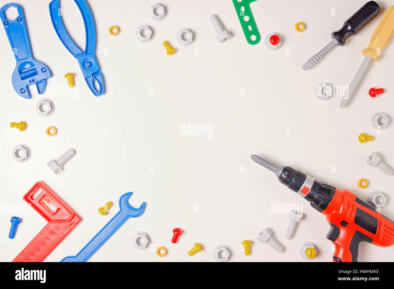 Toys construction tools from kids tool kit frame on white background. Top view. Flat lay. Copy space text - Stock Image