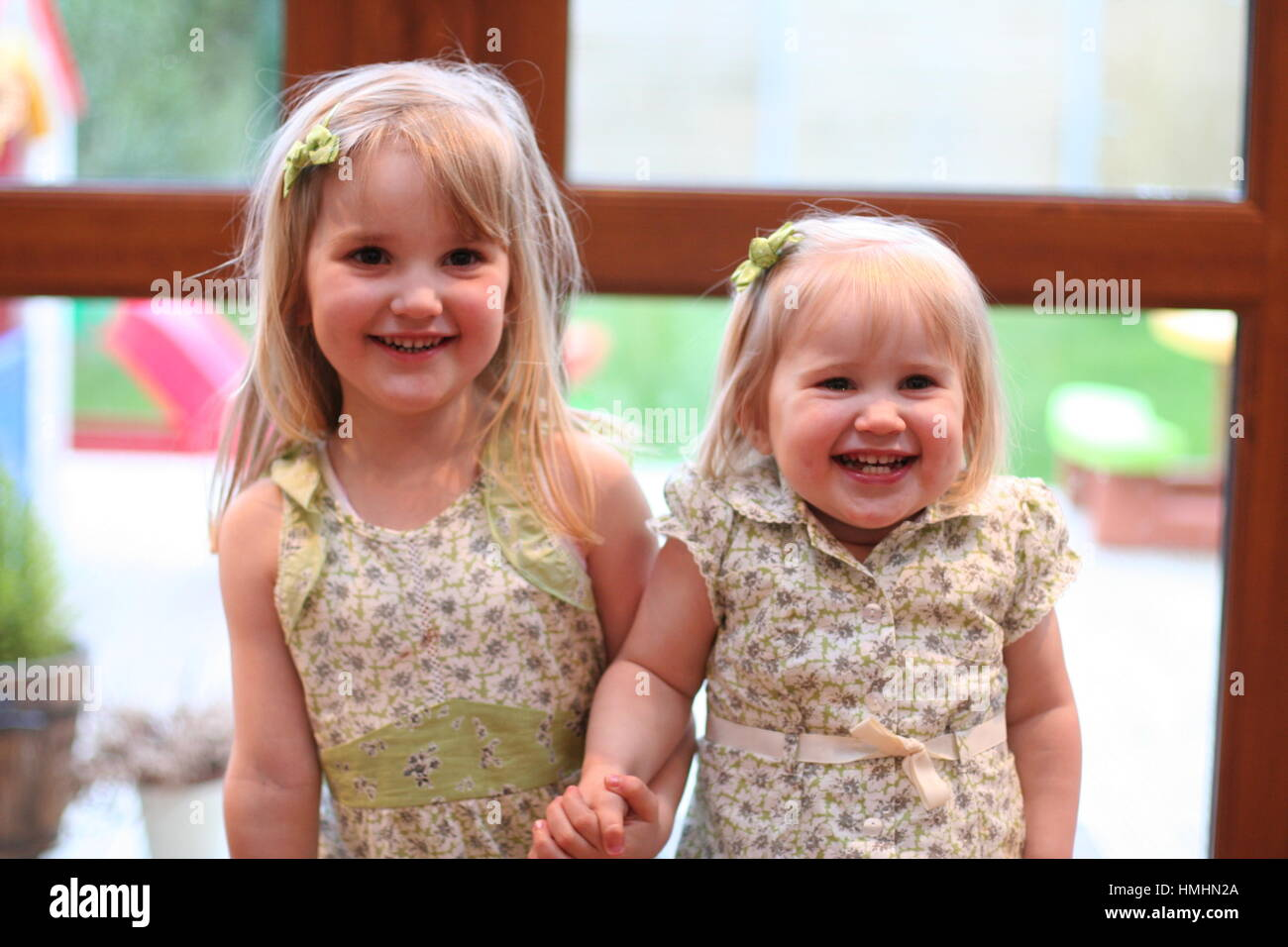 little girls blonde kids big wide smiles face, laughing out loud wearing matching outfits happy blonde children - Stock Image