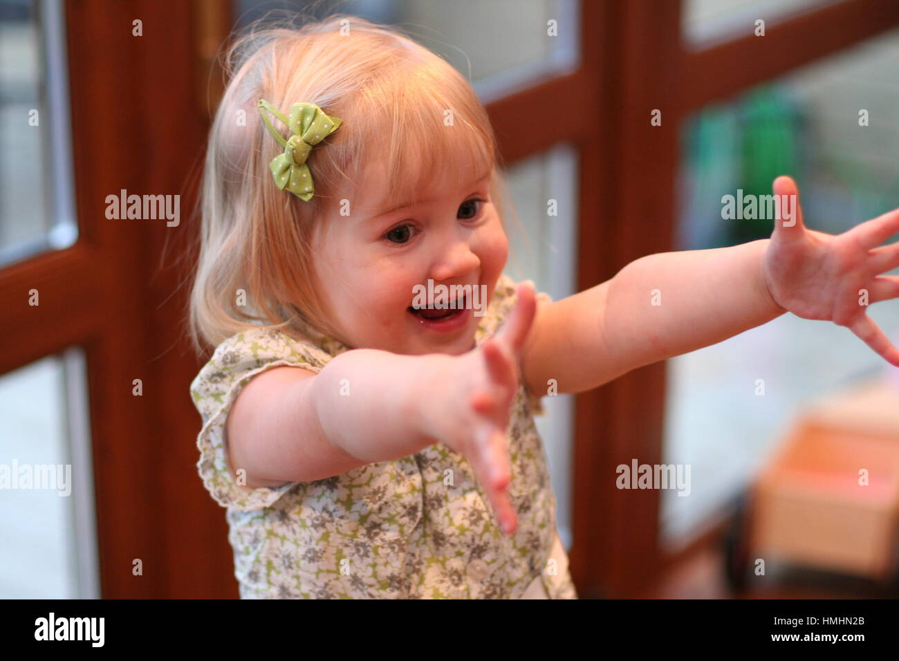 Two year old Little blonde girl toddler child kid arms outstretched delight  big open smile very happy overjoyed - Stock Image