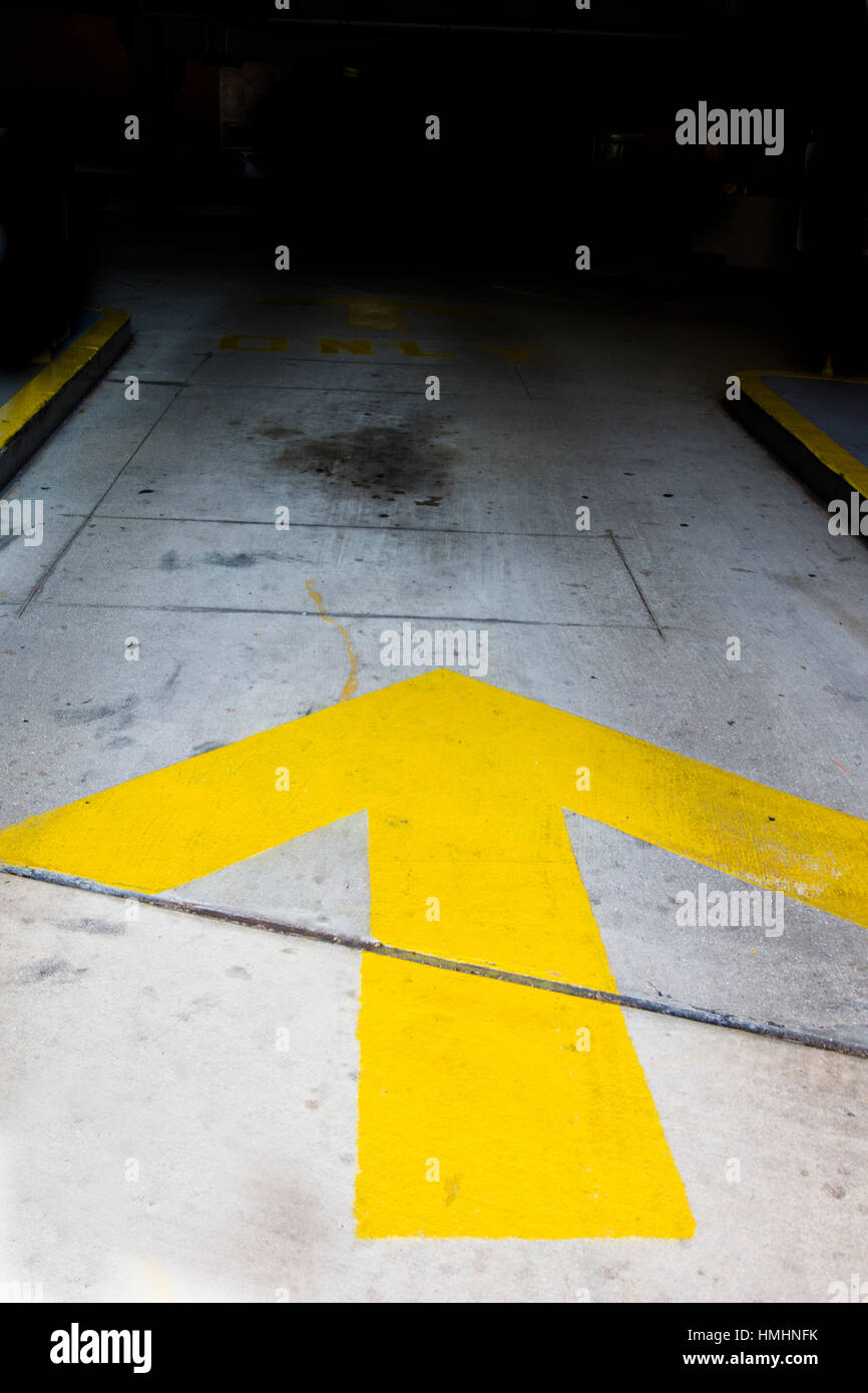 Yellow arrow on pavement leading to darkness - Stock Image