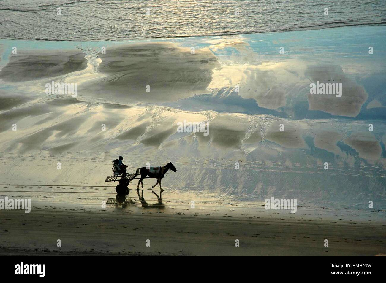 Brazil, Ceara State, Jeriocoacora, a Horse - cart along the Seashore at Sunset. - Stock Image