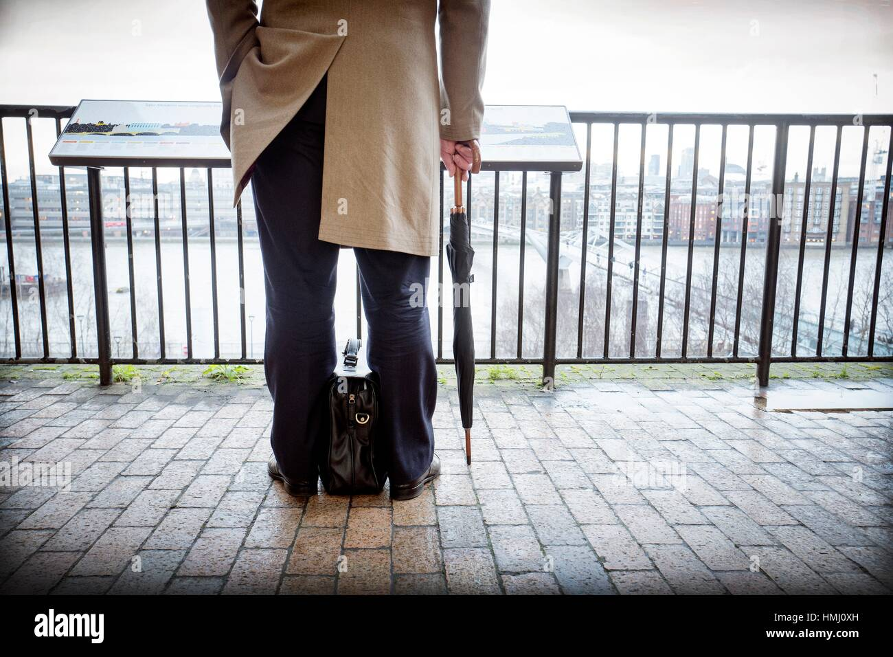 Rear view of unrecognizable businessman, with umbrella and attache case, looking to St. Paul´s Cathedral and - Stock Image