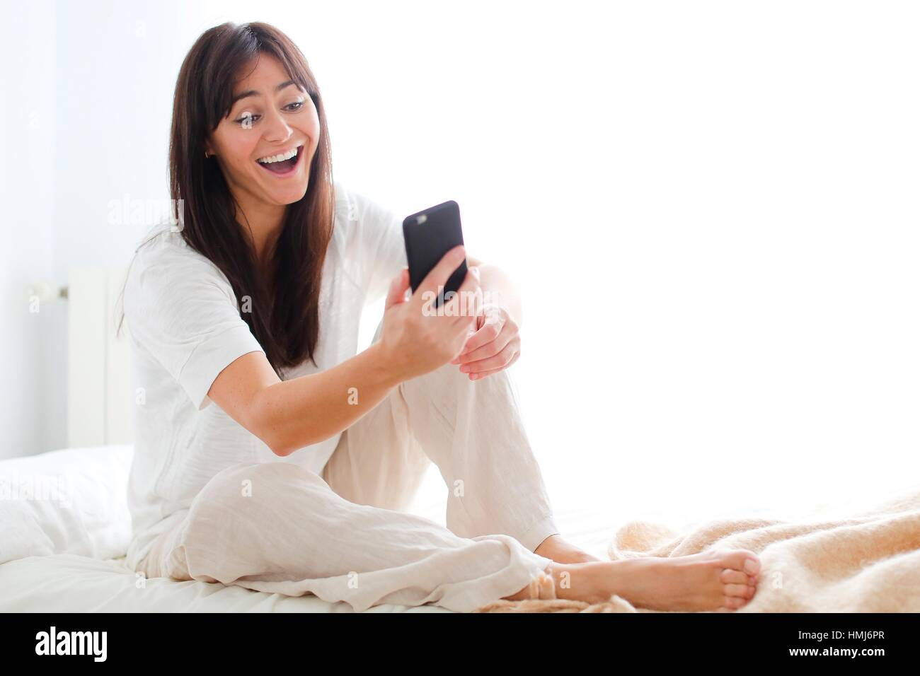 Woman using smartphone showing surprise - Stock Image
