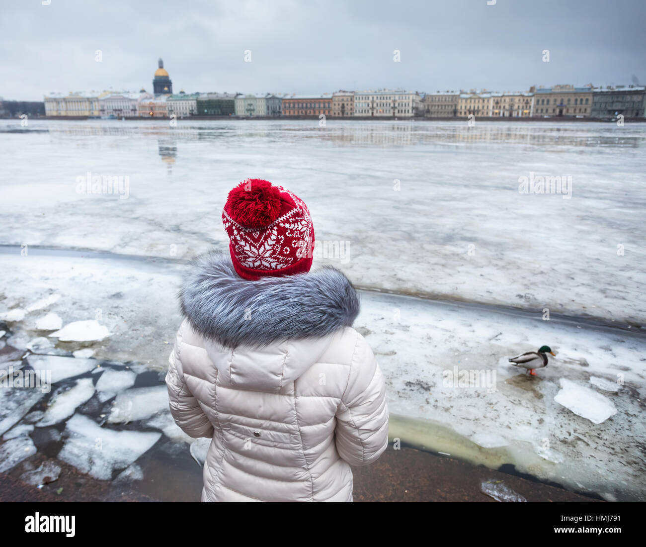 Woman in red hat near frozen Neva River with duck and Isaac's Cathedral on other side in winter Saint-Petersburg, - Stock Image