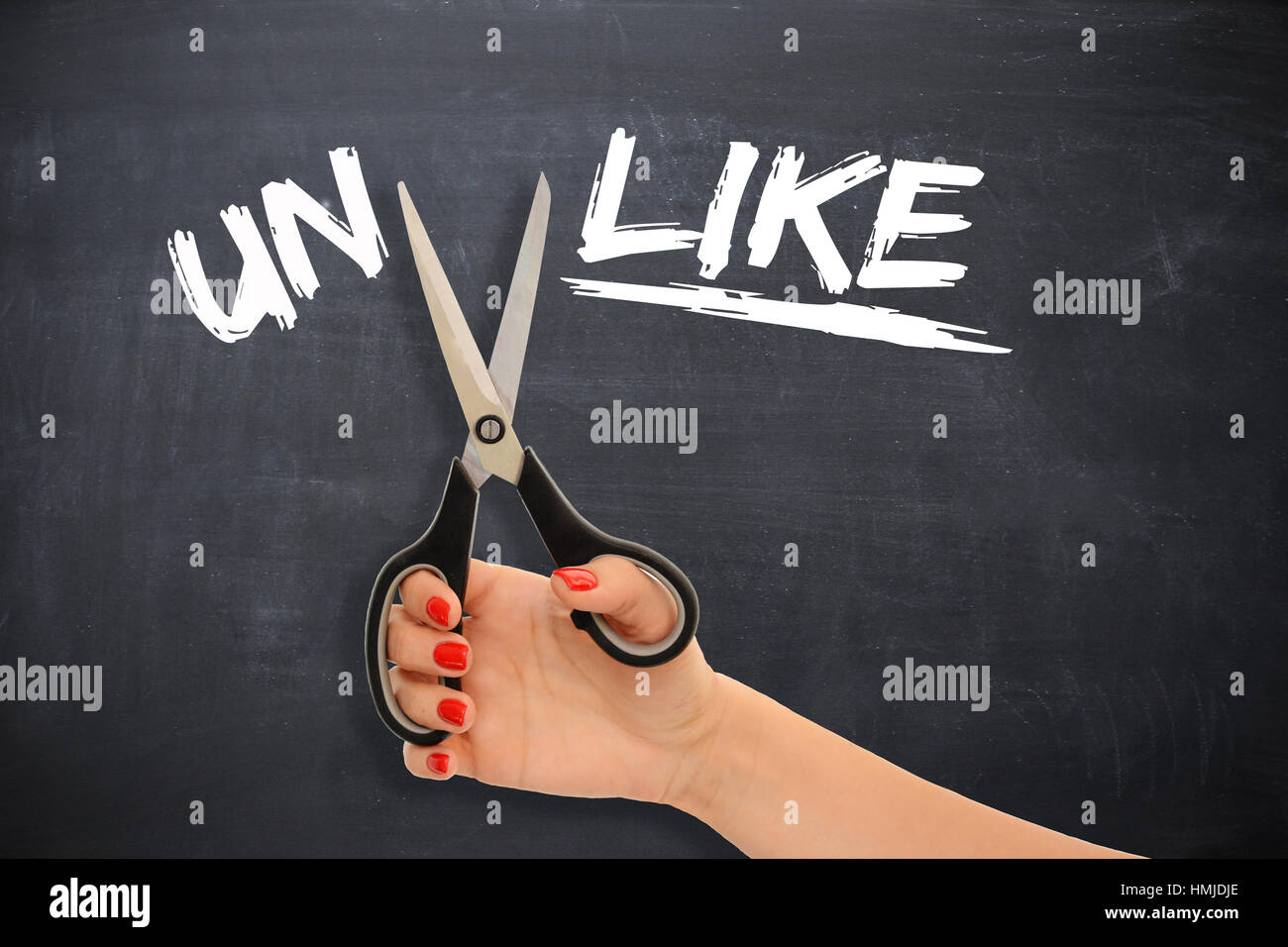 """Woman transforming the word """"unlike"""" to the word """"like"""" by cutting the prefix with scissors Stock Photo"""
