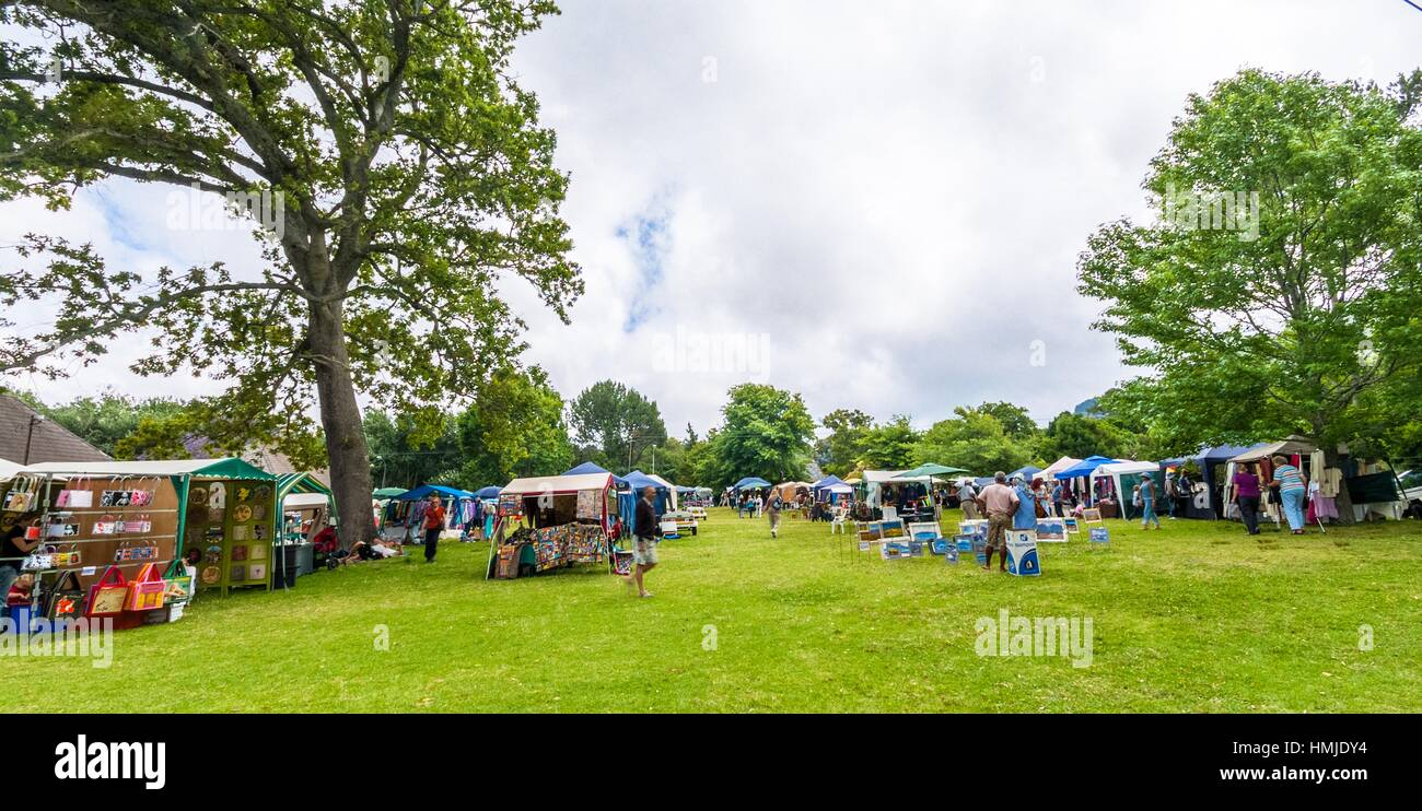 People wander arouns a typical country fair. Under tall oak trees. Cape Town, South Africa. - Stock Image