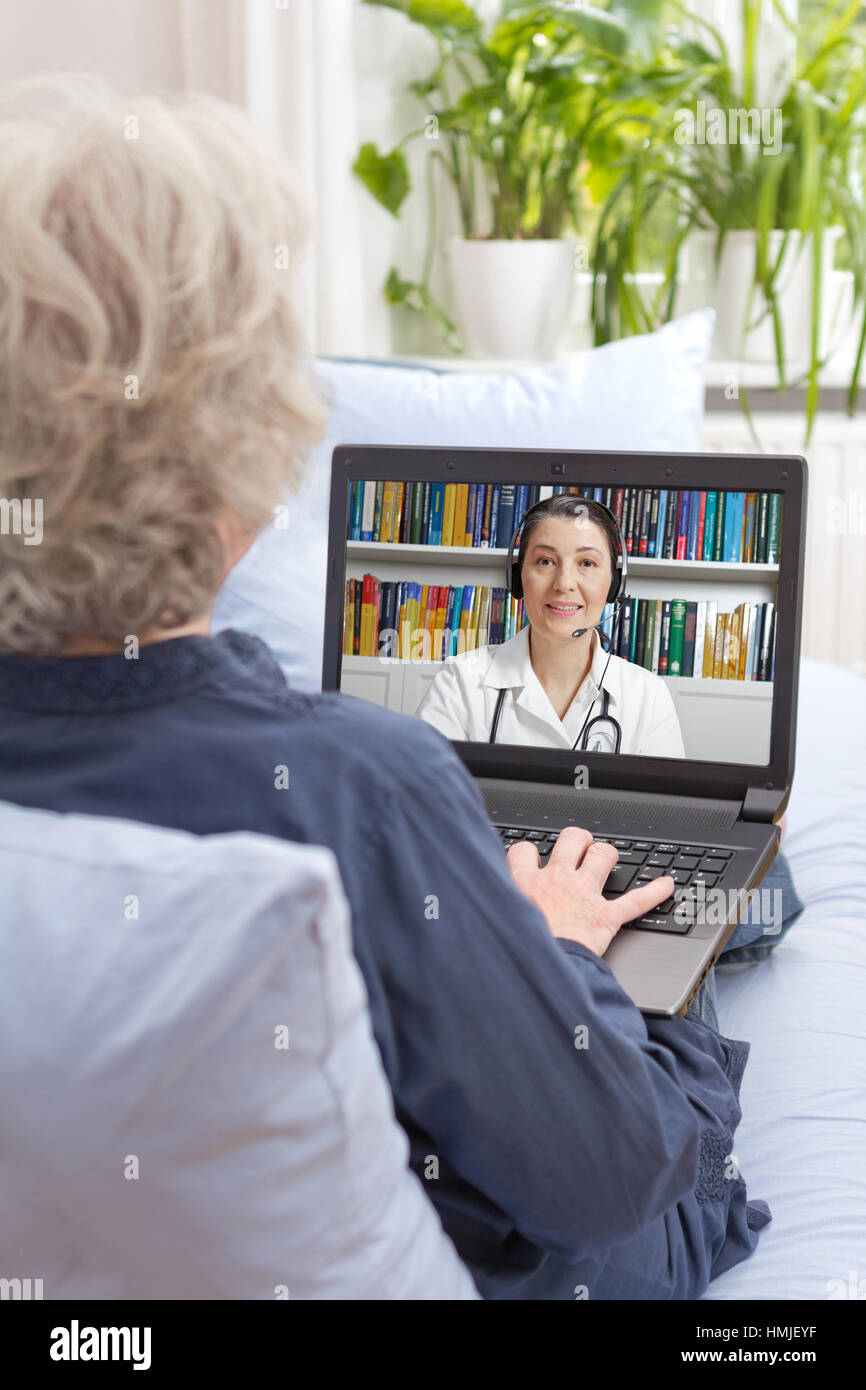 Rear view of an old woman sitting with laptop on the sofa of her living room, having a video call with her physician - Stock Image