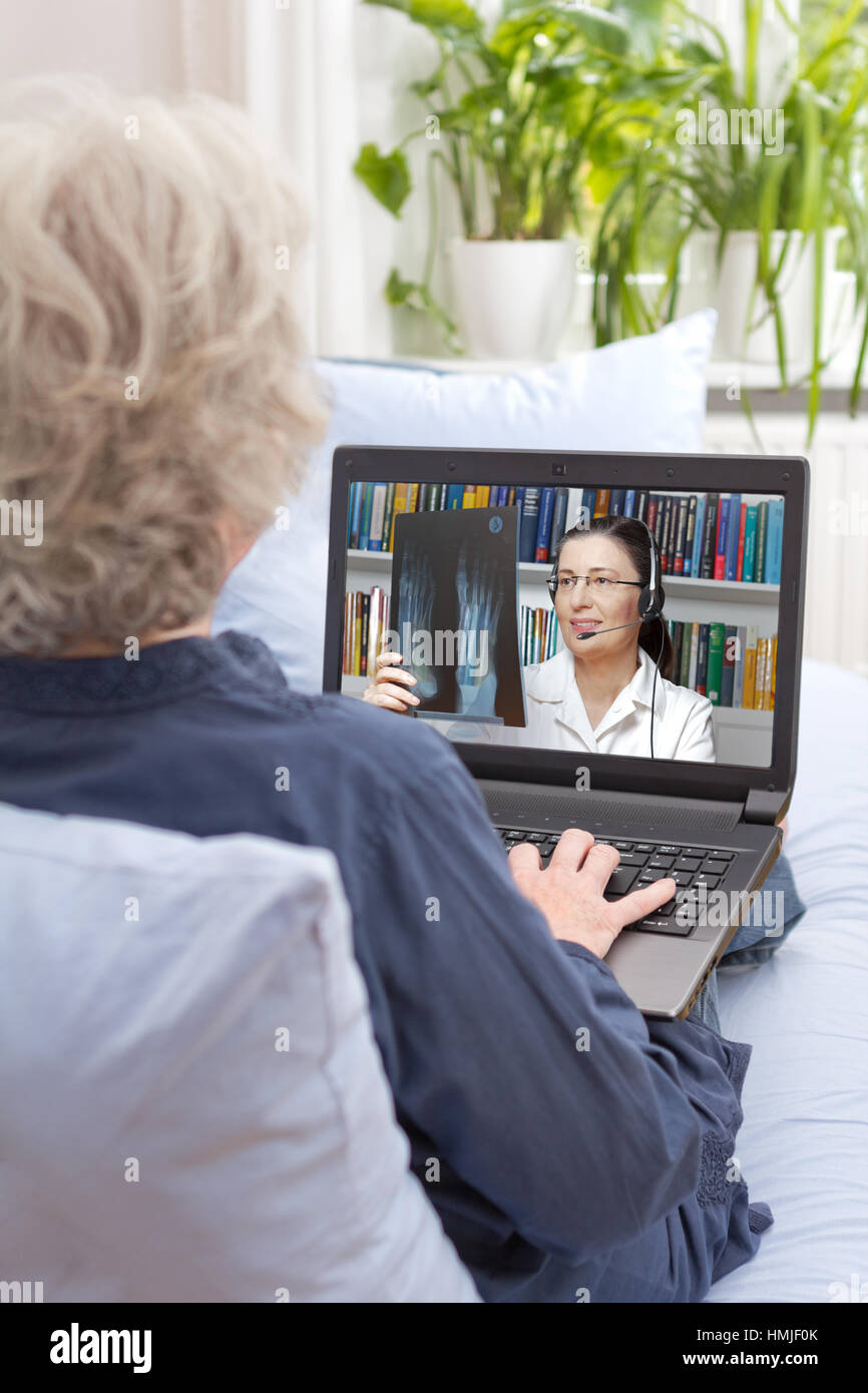 Rear view of a senior woman sitting with notebook on the couch of her living room, having a video call with her - Stock Image