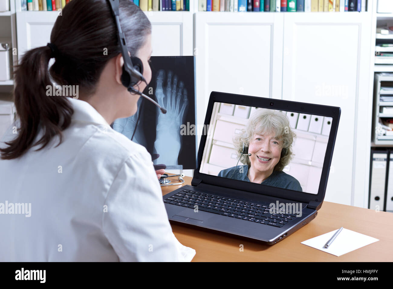 Female doctor in her surgery office with headset in front of her laptop, an x-ray of a foot in hand, talking to - Stock Image