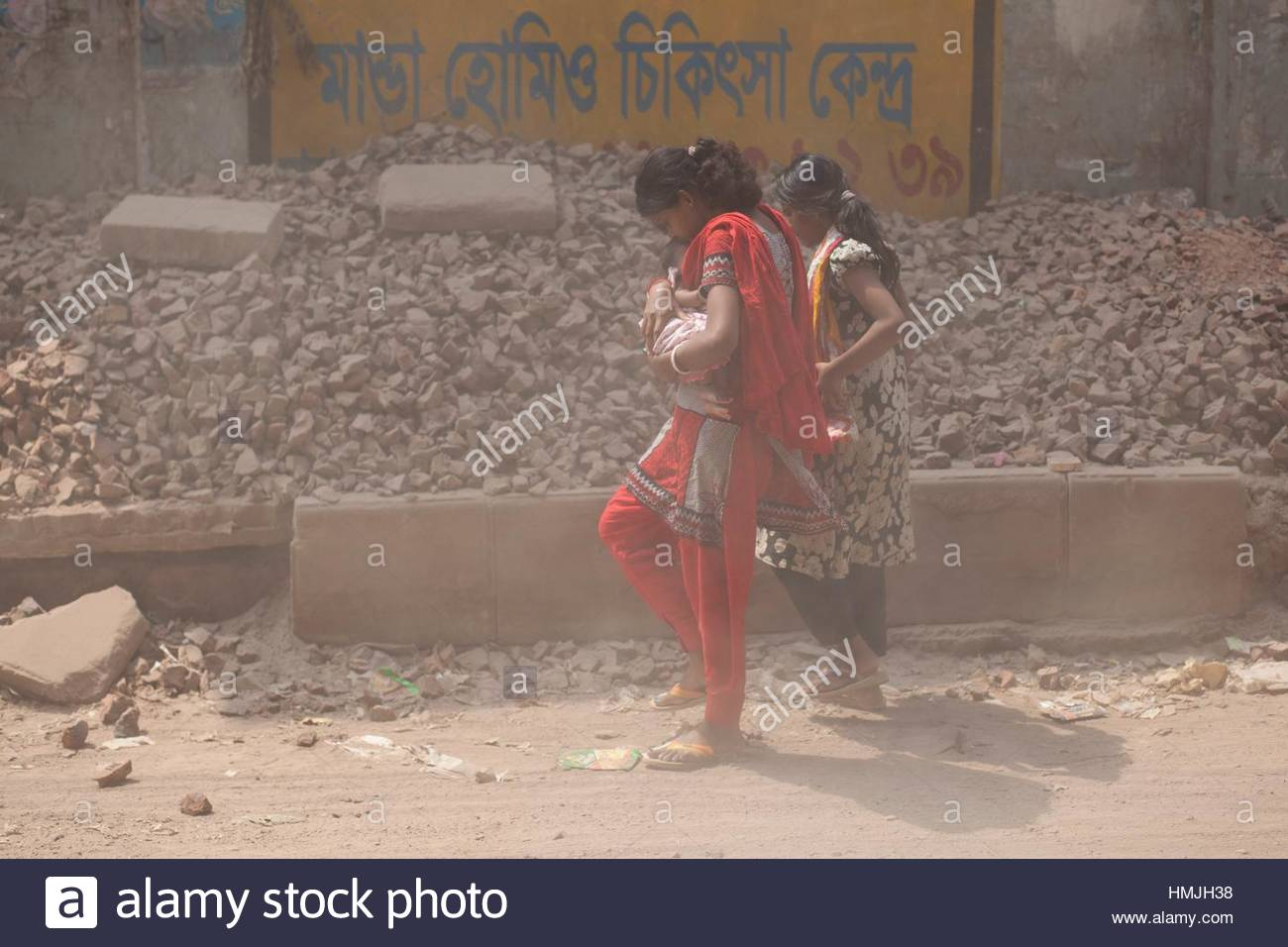 DHAKA, BANGLADESH - MARCH 13 : A mother with her new born child move fast to save from air dust on a busy street - Stock Image