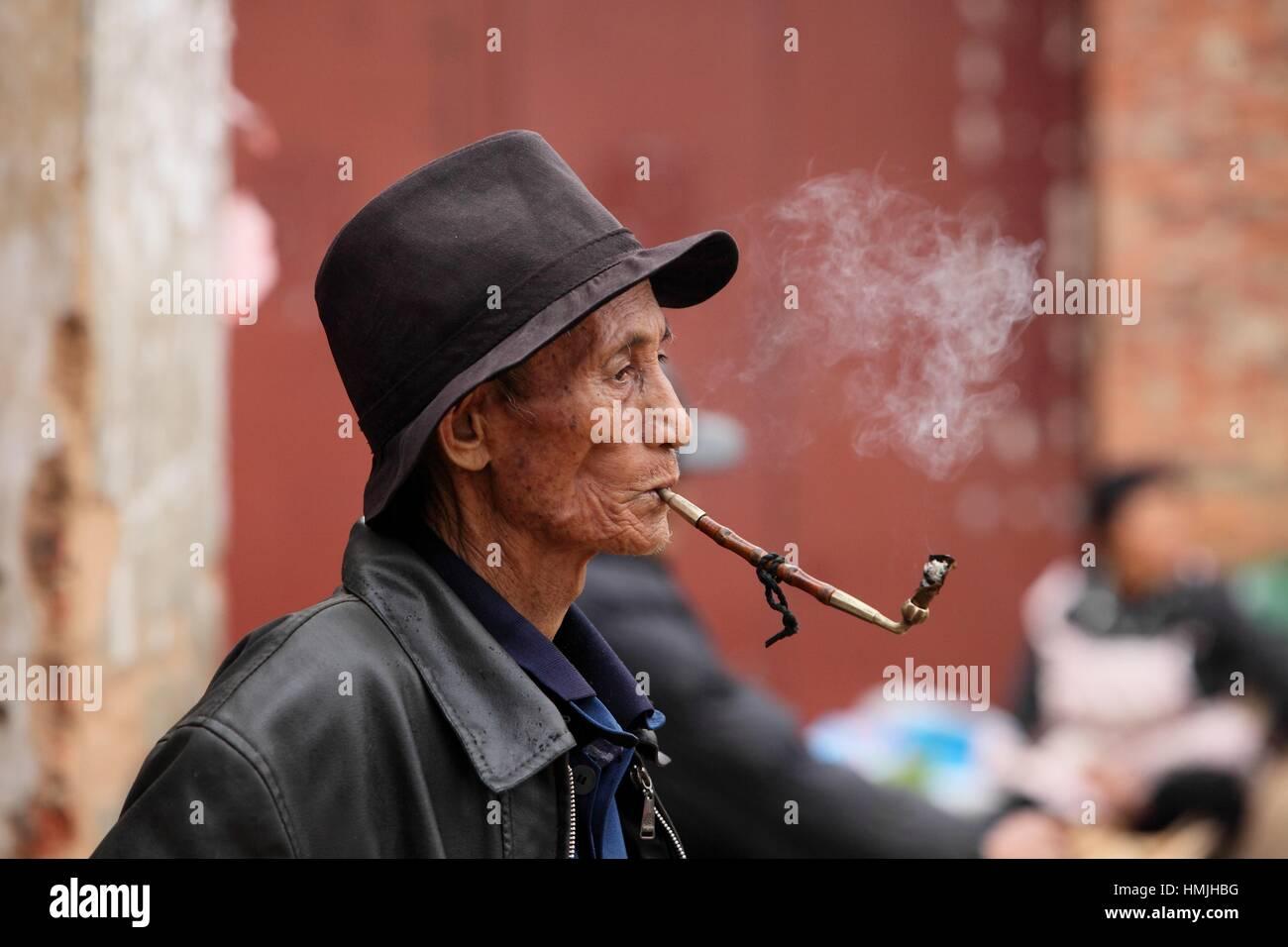 Old chinesse man smoking a pipe, Yunnan province, China - Stock Image