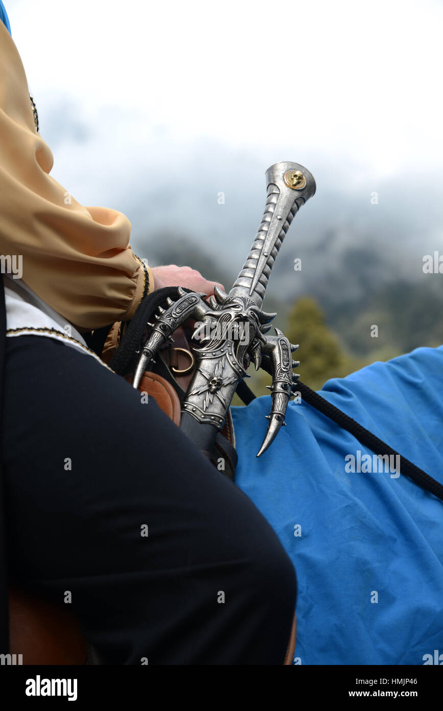 An actor in period costume with a gothic sword sits astride his horse - Stock Image