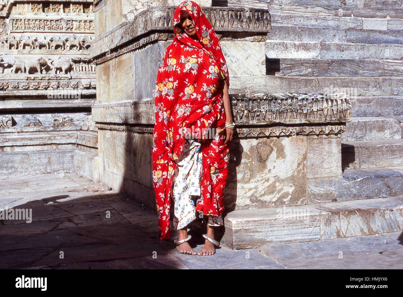 View of a beggar woman in red cloth posing in front of wall carvings at the Jagdish Temple complex, in Udaipur, - Stock Image