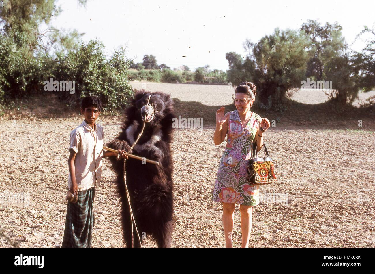 Scene of a Western woman hesitantly posing with a young Indian boy and his muzzled, leashed black bear outside the - Stock Image