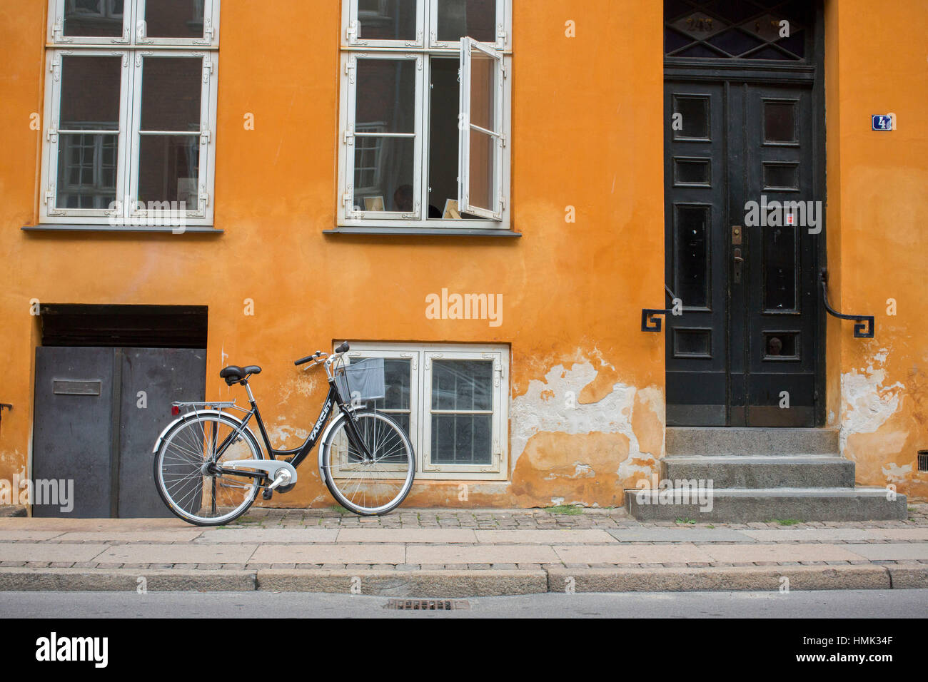 Bike against Orange Wall Copenhagen, Denmark - Stock Image