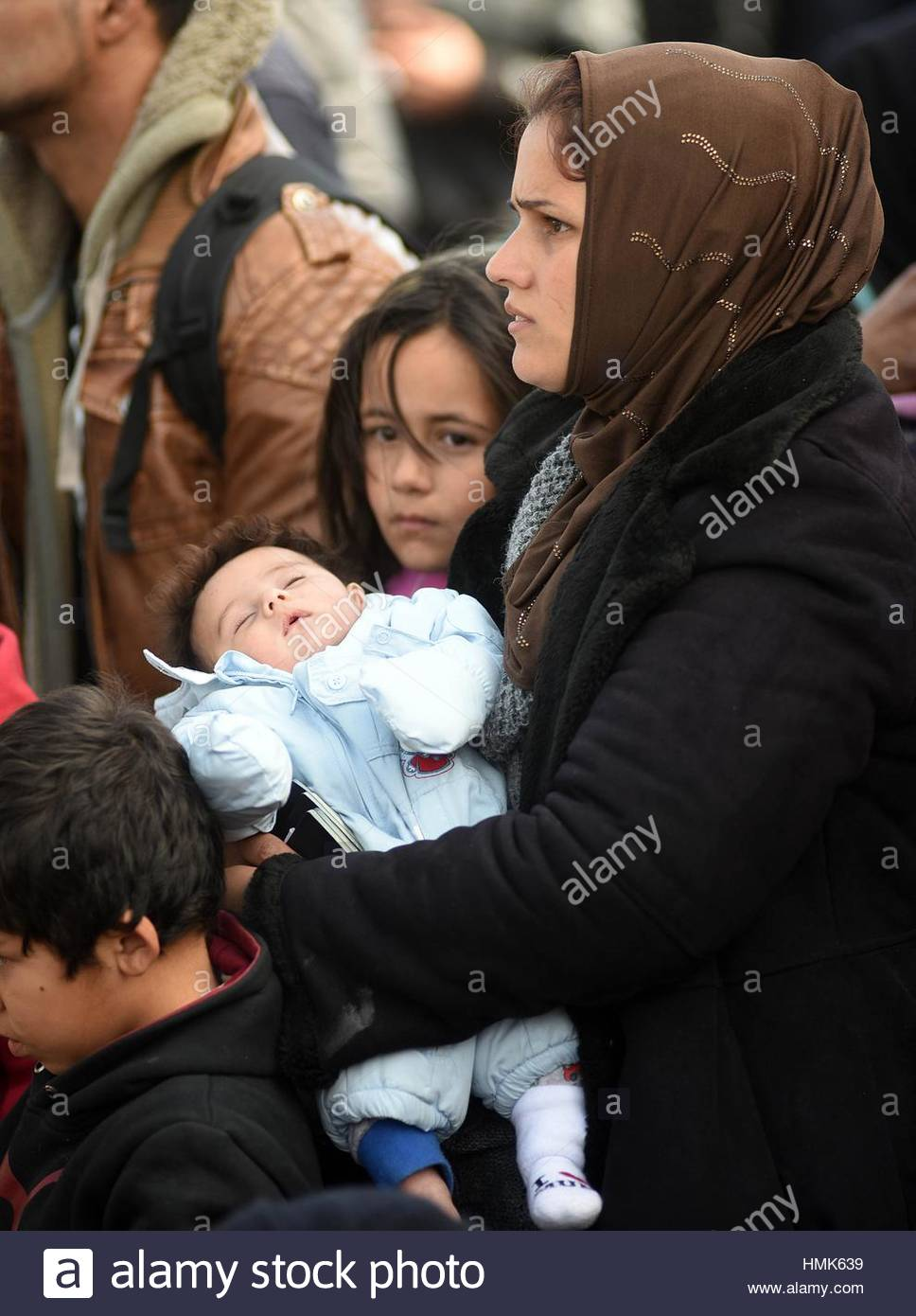 Refugges and migrants wait to be allowed to cross the border to Macedonia in the northern Greek border station of - Stock Image