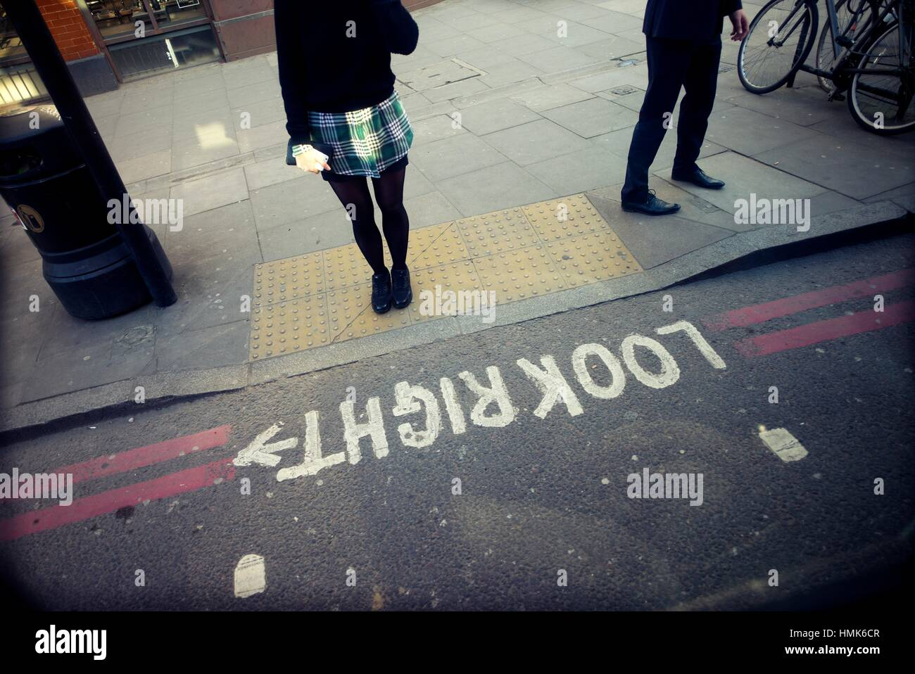 Unrecognizable young girl with miniskirt waiting to cross a street. Look right. London, England, UK, Europe. - Stock Image