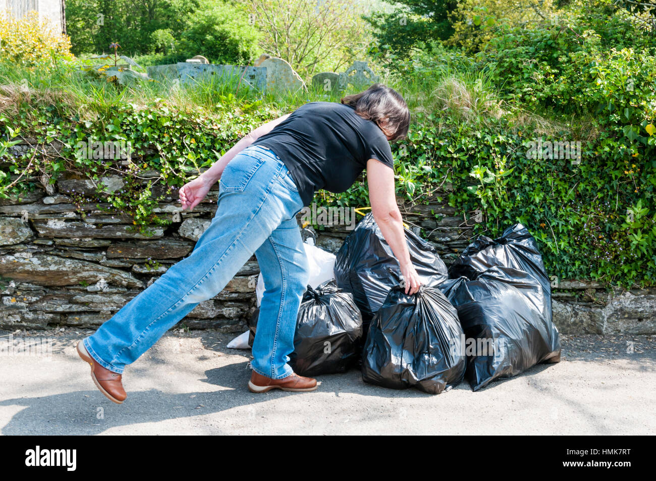 Putting out rubbish in black sacks for collection. In rural Cornwall. - Stock Image