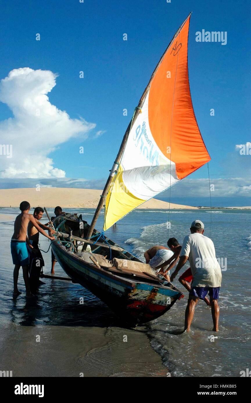 Brazil, Ceara State, Jericoacoara, Fishing Boat and Fishermen along the Beach. Stock Photo