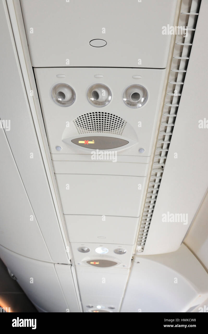 overhead fresh-air vents no smoking sign in economy-class cabin Singapore Airlines Airbus A380 enroute flight-number - Stock Image
