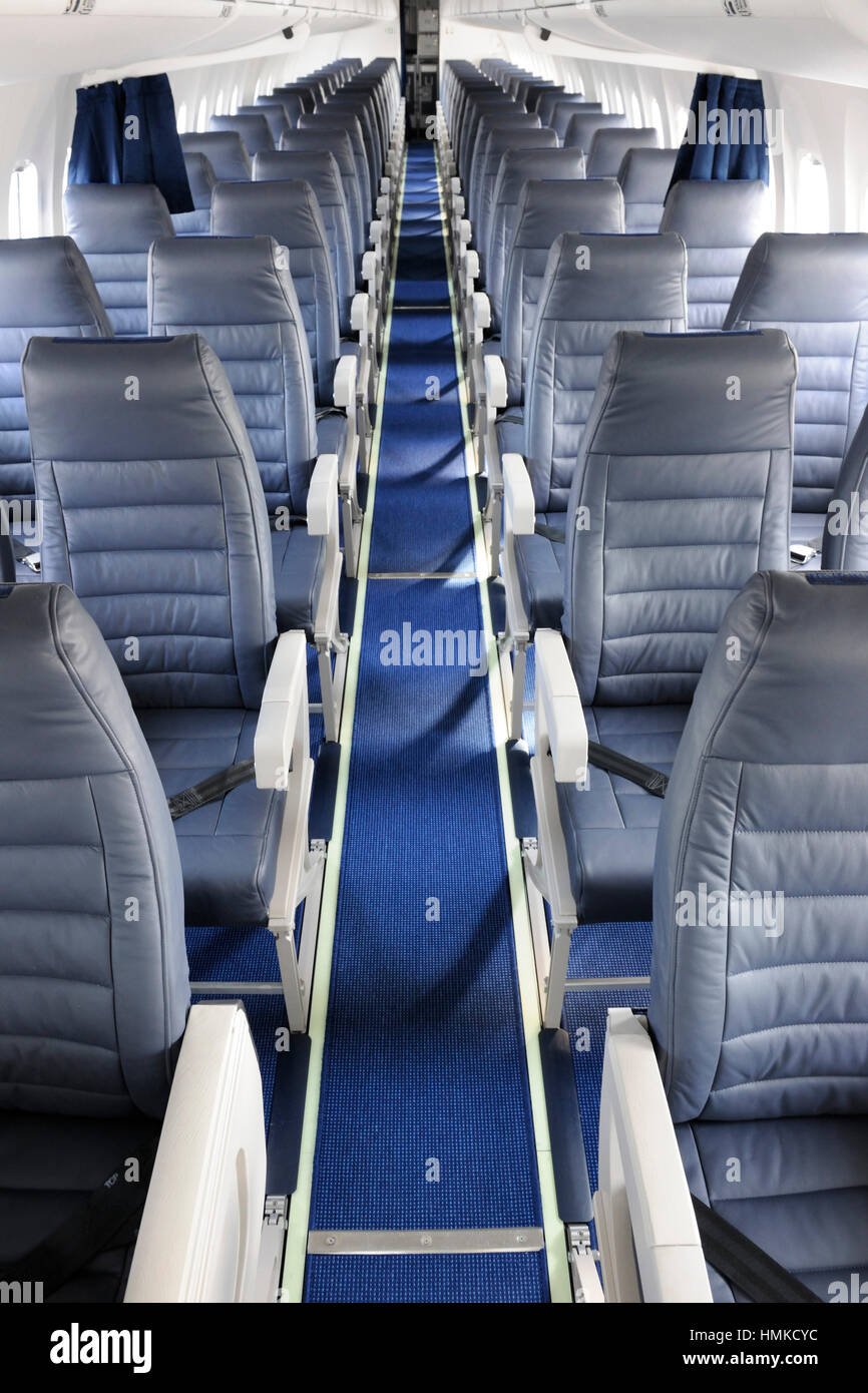 aisle empty passenger cabin seats on AirBaltic Bombardier DHC-8 Q400 Next Generation parked in static-display at - Stock Image