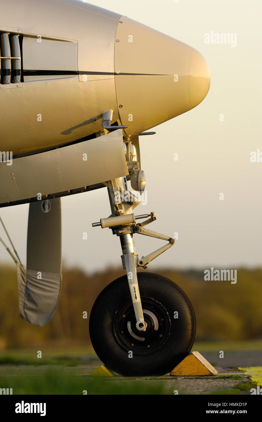 nosewheel undercarriage with a chock of Synergy Aviation Beechcraft King Air B200 parked - Stock Image
