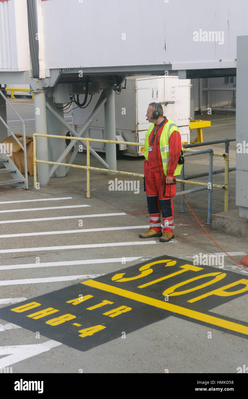 man wearing headset with orange and yellow high-viz tabard standing on parking stop sign markings for DHC8 Q400 - Stock Image