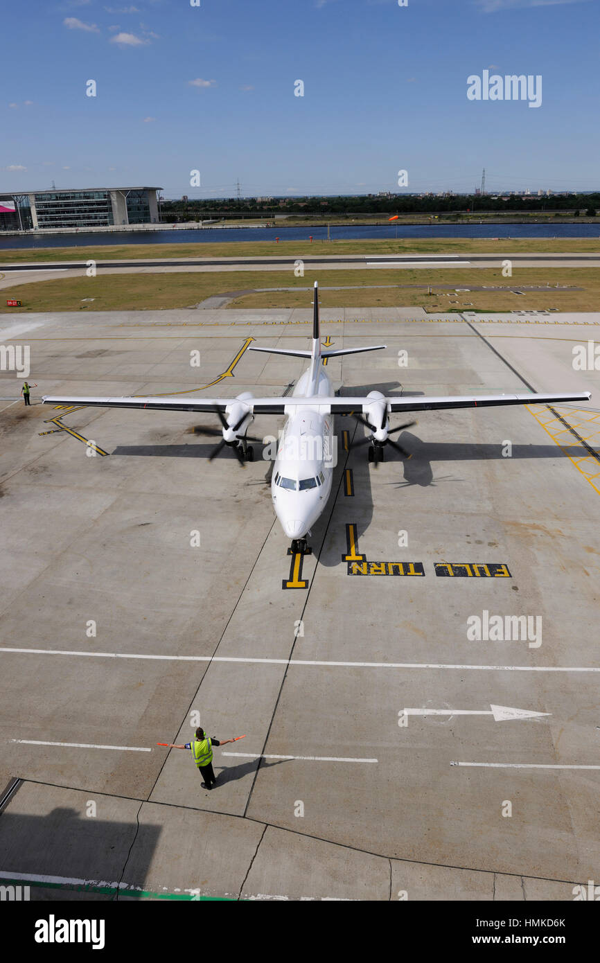 marshaller with bats controlling CityJet Fokker F-50 taxiing at London City - Stock Image