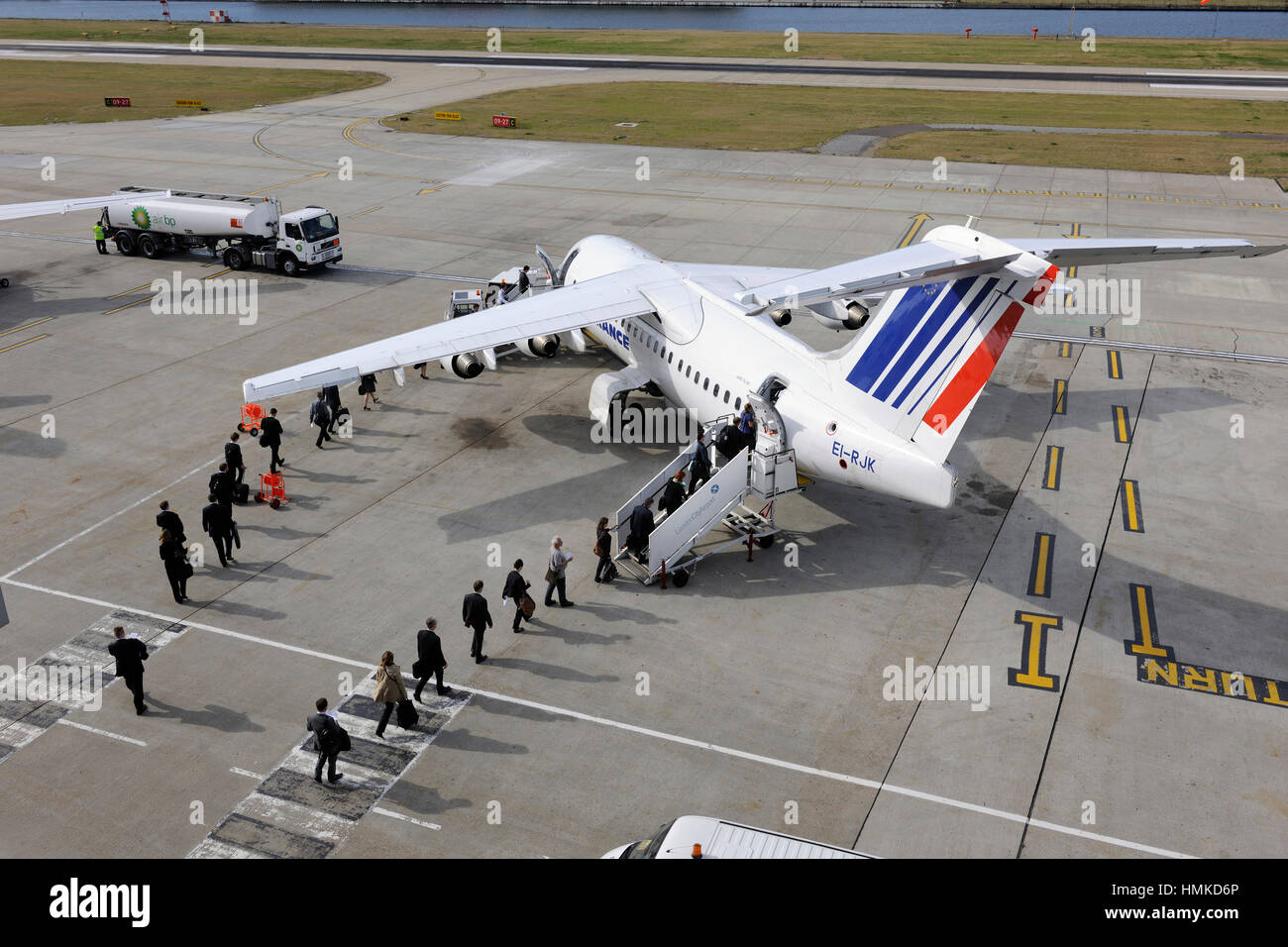 passengers carry-on bags boarding Air France - CityJet BAE 146 Avro RJ-85 parked Air BP Refuelling bowser behind Stock Photo