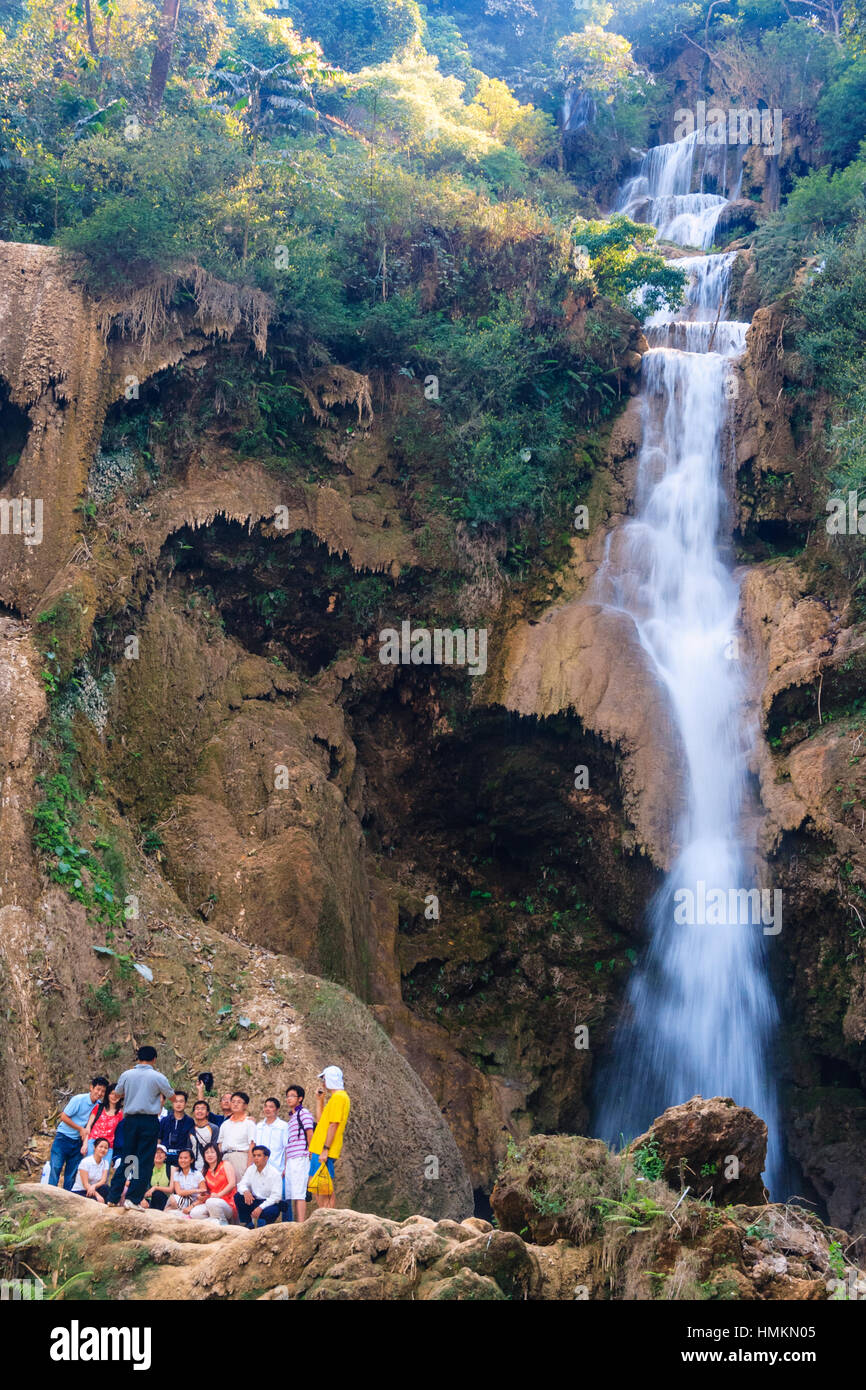 A group of tourists pose for a picture by Kuang Si Waterfalls, 29 km south of Luang Prabang, Laos, South East Asia - Stock Image