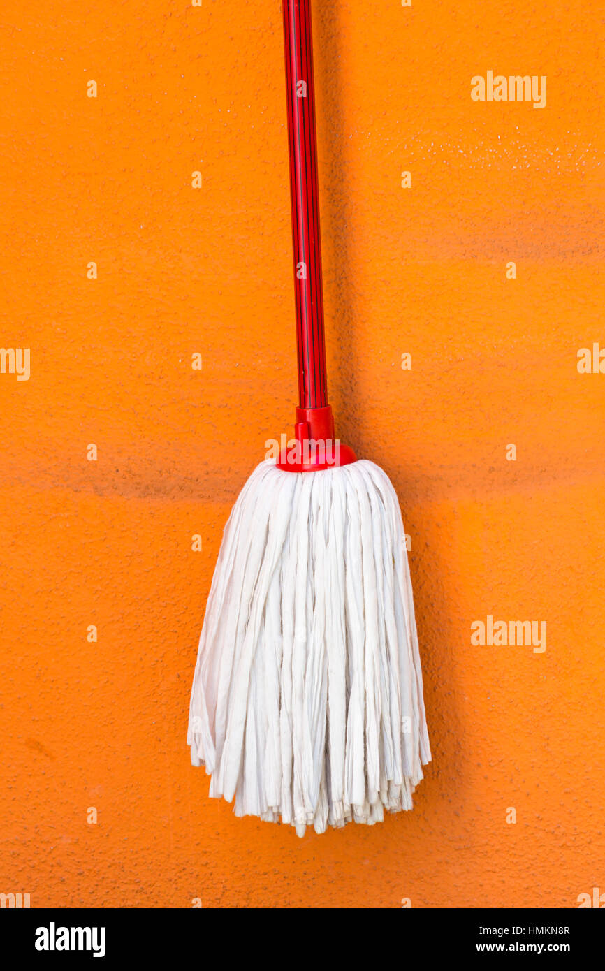 Mop hanging from colourful wall of brightly coloured house in Burano - bright colors of Burano, Venice, Italy in - Stock Image