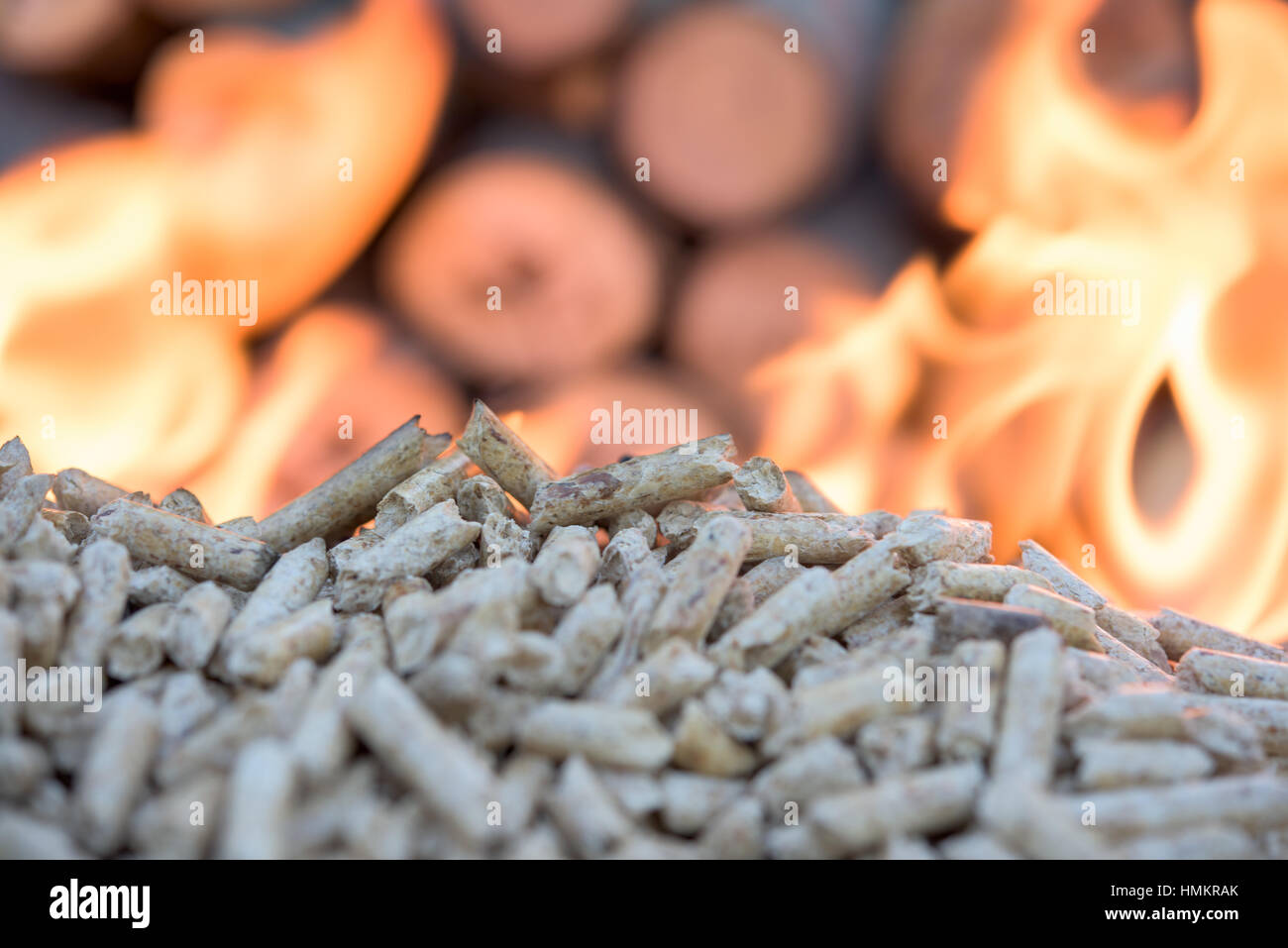 wooden Biomass in flames infront wall of wood - Stock Image