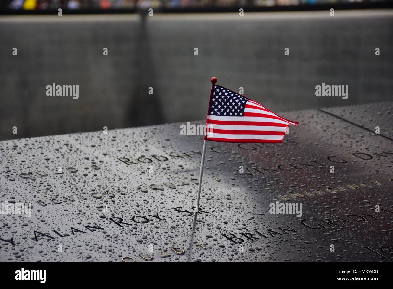 Memorial at Ground Zero Manhattan for September 11 Terrorist Attack with an American Flag Standing near the Names - Stock Image