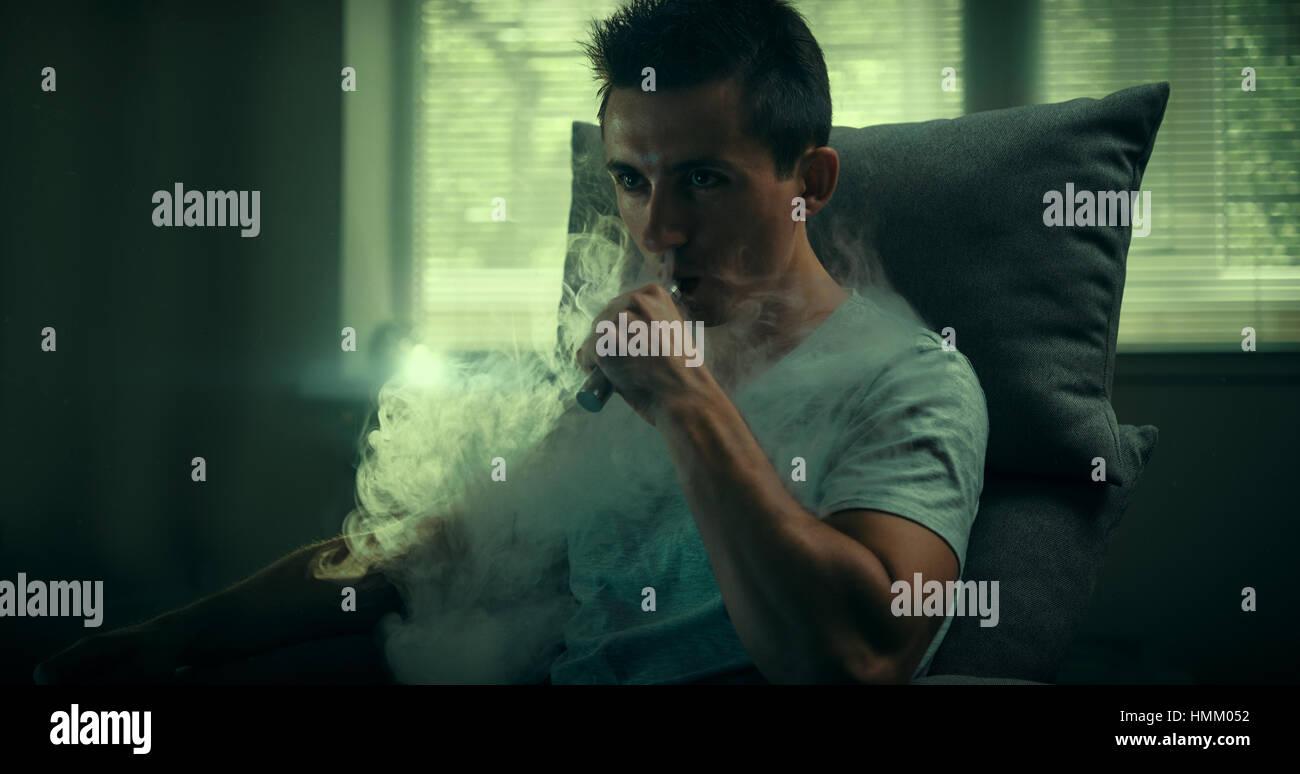 Stylish vaper. Young guy. Man using an advanced personal vaporizer or e-cigarette. - Stock Image