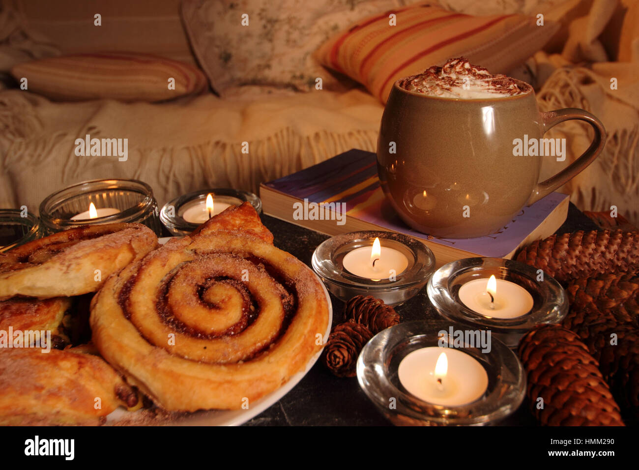 A cosy,candle lit corner in an English home inspired by the Danish concept of hygge with pastries, hot drink,a good - Stock Image