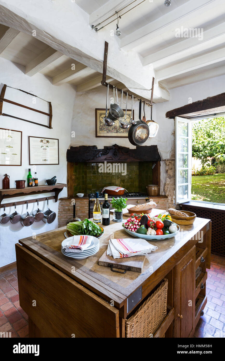 French Country Kitchen With Range Hanging Pans And Butchers Block Stock Photo Alamy